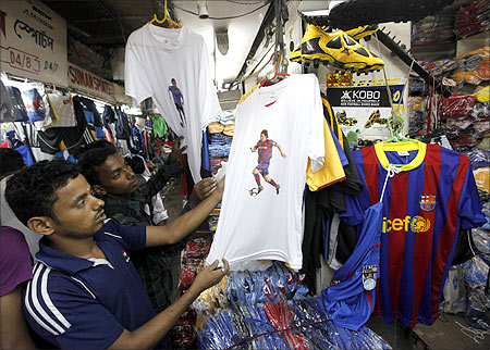Soccer fans shop for t-shirts and jerseys featuring Argentinan and Venezuelan soccer players at a sports goods market in Kolkata.