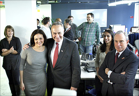 US Senator Charles Schumer (3rd L) hugs Facebook's Chief Operating Officer (COO) Sheryl Sandberg (2nd L) next to New York City Mayor Michael Bloomberg (R).