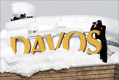A member of Swiss special police forces observes from the roof of a hotel covered in snow in Davos.