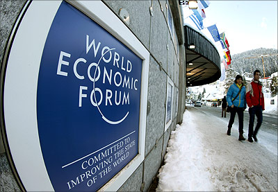 People walk past the logo of the World Economic Forum in front of the congress centre in Davos.