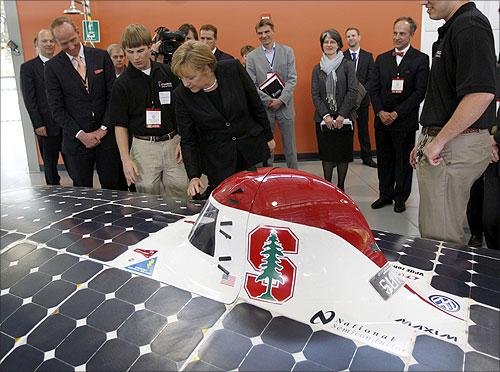 German Chancellor Angela Merkel (C) looks at a solar car.