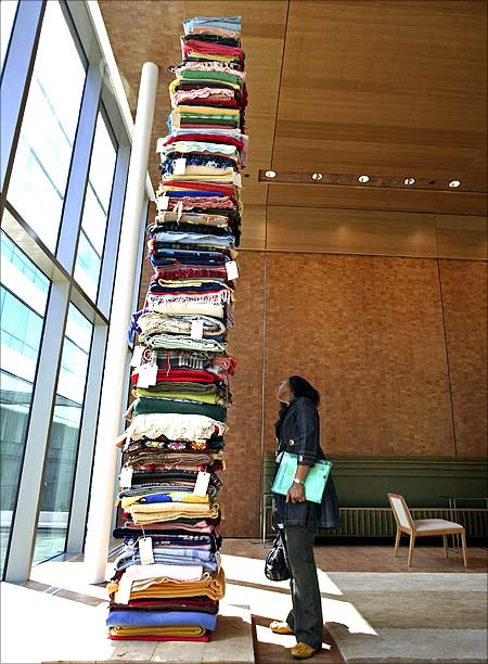 Valerie Watt looks at art installation story blankets by artist Marie Watt in the reception area.