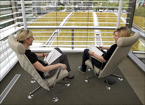 New-media employees Jennifer Hauseman and Tyler LePar have a conference on what staff like to call the diving platform on the sixth floor.