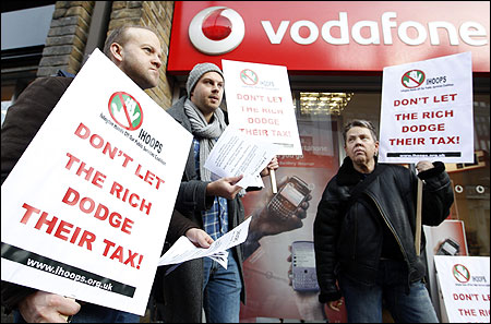 Demonstrators stand poutside a branch of Vodafone as they protest against the company not paying enough tax.