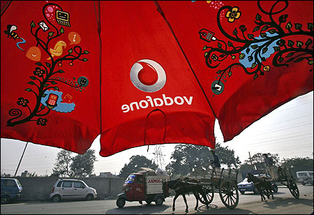 Men ride their horse carts past an umbrella with a Vodafone logo on a road in Jammu.