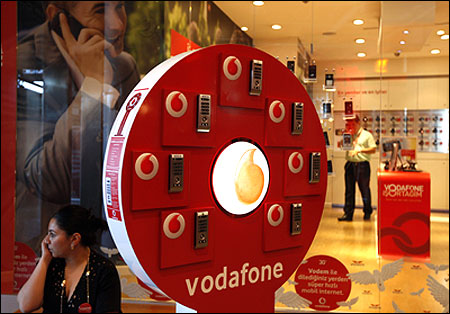 A woman talks on her mobile phone in front of a Vodafone store in Istanbul.