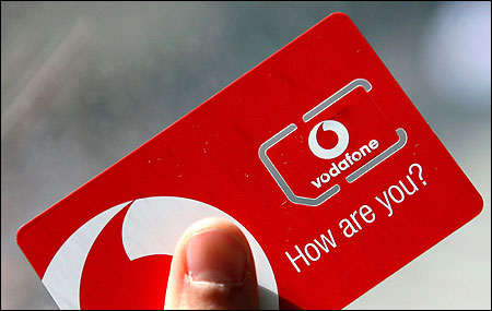 A woman holds a Vodafone sim card in central London on May 30, 2006.