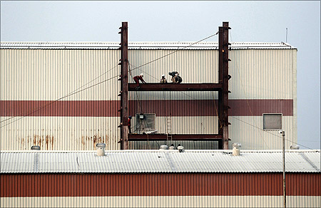 Labourers work at a factory under construction at Hajipur industrial park on the outskirts of Patna.