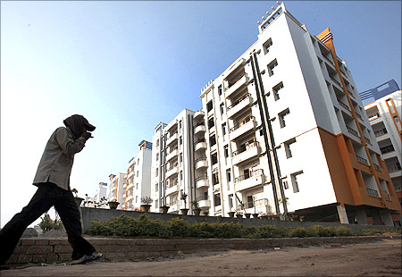 A labourer walks past residential apartments in Patna.