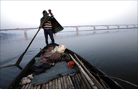 A man rows his boat in the waters of river Ganges with Mahatma Gandhi Setu bridge.