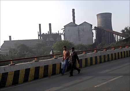 People walk past a closed sugar mill in Patna.