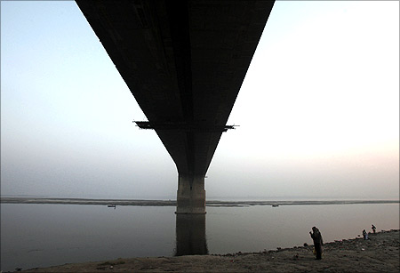 A man stands under the Mahatma Gandhi Setu bridge built over river Ganges.