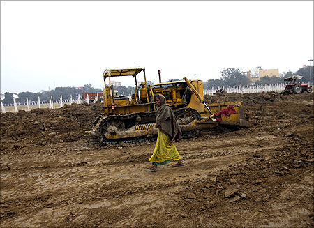 A woman walks past a bulldozer at a park being renovated in Patna.