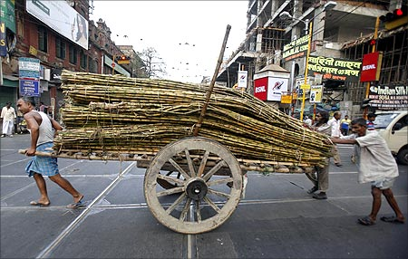 Labourers transport sugarcane on a hand-cart outside a wholesale market in