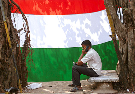 man speaks on the phone outside his shanty in front of an Indian national flag in Dharavi.