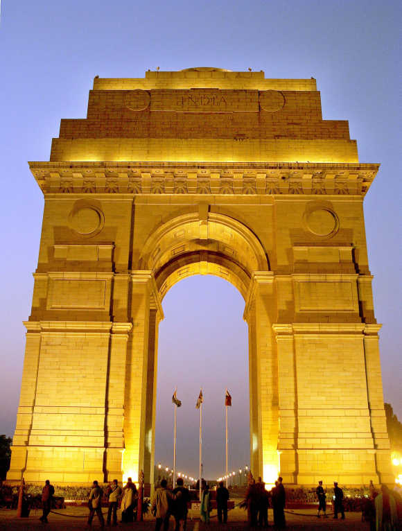 People walk near the historic India Gate during evening in New Delhi.