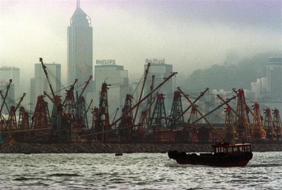 A lone sampan floats by barges inside a typhoon shelter in Victoria harbor on June 22, 1997, as a low mist covers the skyscrapers of Hong Kong.