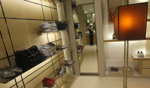 An employee is reflected in a mirror as she waits for customers inside a showroom at the Emporio mall in New Delhi.