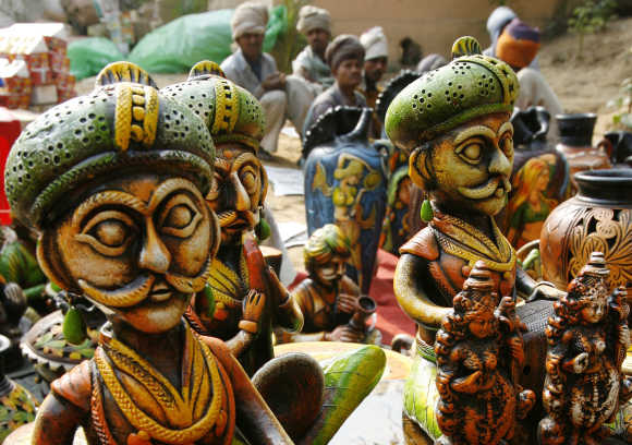 Labourers sit near a stall of sculptures at Surajkund Crafts Fair in Haryana.
