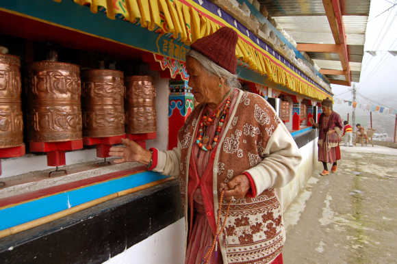 An elderly lady of the Manpa tribe spins prayer wheels at a monastery in Tawang, in Arunachal Pradesh, near the border with China.