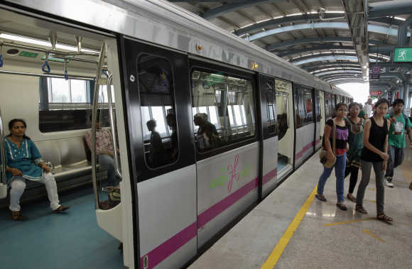Commuters disembark from a Metro at an elevated station in the Indira Nagar area of Bangalore.