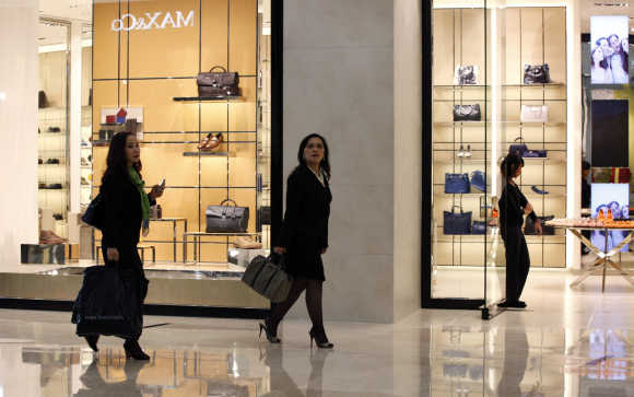 Women walk past a shop selling luxury shoes and bags at a shopping mall in Jakarta.