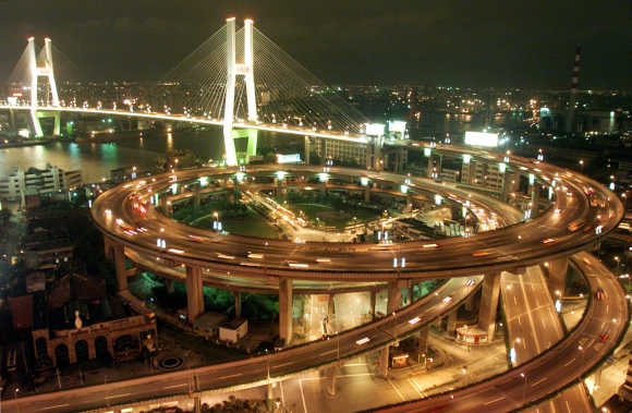 Vehicles pass through teh brightly-lit Nanpu Bridge in Shanghai.