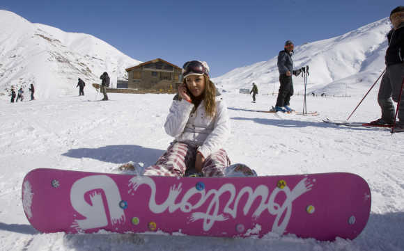 A woman speaks on her mobile phone at the midway point of a slope at Shemshak ski resort, Iran.