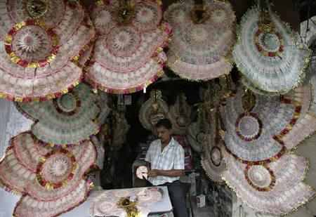 A shopkeeper staples currency notes to make garlands.