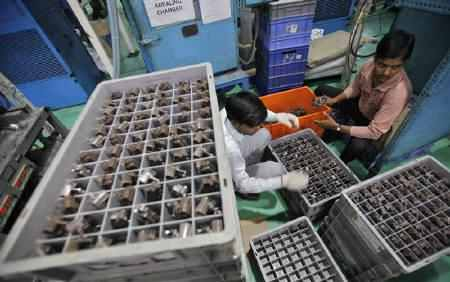 Employees pack auto components at the factory an auto parts making company