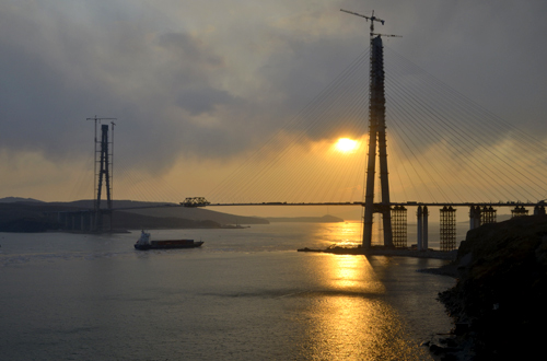 The sun sets behind a bridge under construction linking Russky Island (R) to the mainland, near Russia's far Eastern port of Vladivostok.