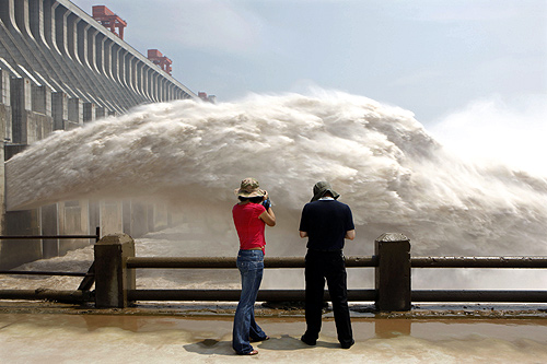 Journalists take pictures as the Three Gorges Dam discharges water to lower the level in its reservoir in Yichang, Hubei province.