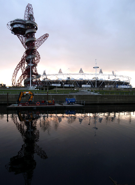 Olympic stadium and Anish Kapoor's ArcelorMittal Orbit tower are reflected in a canal in Stratford, east London.