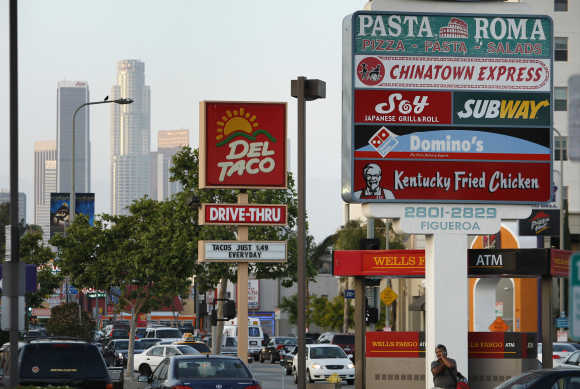 Signs of fast food restaurants are seen along a busy street in Los Angeles.