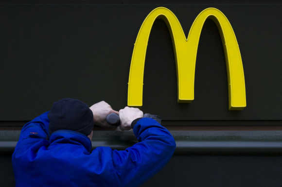 A worker drills a hole underneath the McDonald's brand sign at a store of the global fast food chain in Berlin.