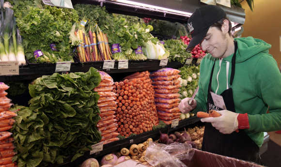 Whole Foods grocery store worker Tim Owen trims the tops of organic carrots in the produce section of the store in Ann Arbor, Michigan.