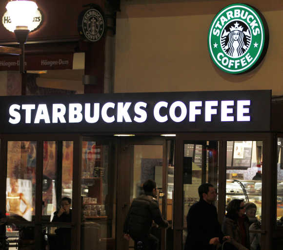 Customers are seen at a Starbucks coffee store, which displays the old logo in Paris.