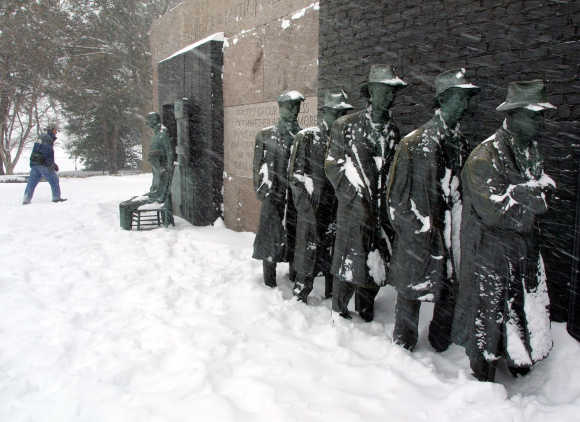 A driving blizzard blows on a Great Depression Bread-Line sculpture as a hiker walks by at the FDR Memorial in Washington, DC.