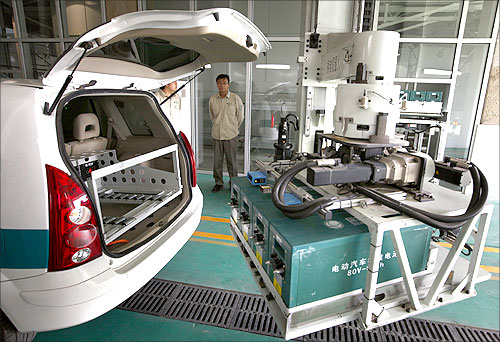 Workers watch as a battery exchange robot changes the batteries in an electric car at China's largest electric vehicle battery recharging station in Beijing.
