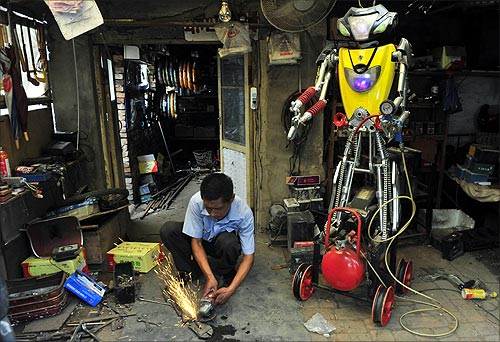 A 49-year-old electric bike mechanic who identified himself only as Wu welds a component to fit onto his newly-made robot (R) at his repair shop in Shenyang, Liaoning province.