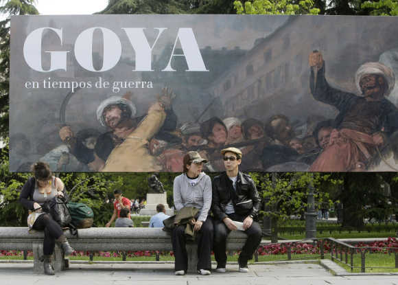 People sit in front of a banner announcing Goya exhibition in Madrid.