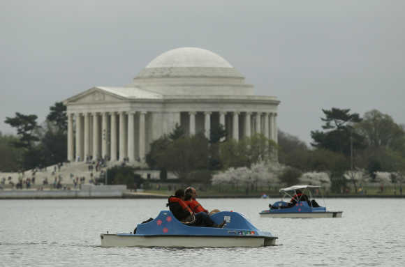 People paddle boat on the Tidal Basin with the Jefferson Memorial in the background in Washington, DC.