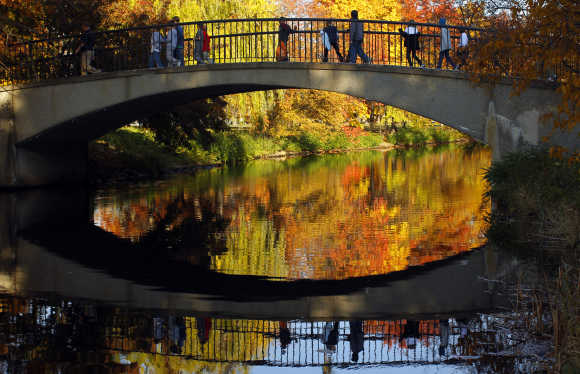 Children cross a footbridge on the Esplanade on an unusually warm fall day in Boston.