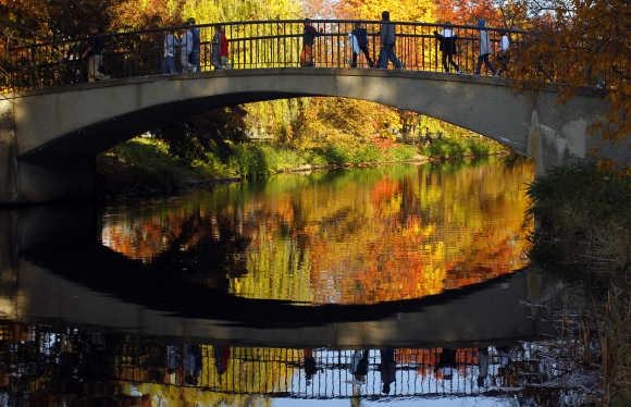Children cross a footbridge on the Esplanade on an unusually warm fall day in Boston.