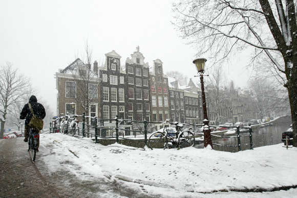 A cyclist makes his way over a snow covered bridge in the Dutch capital of Amsterdam.