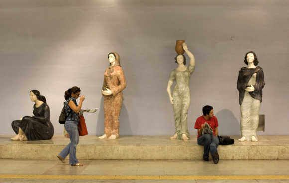 Passengers wait for their trains at Lisbon's subway station.