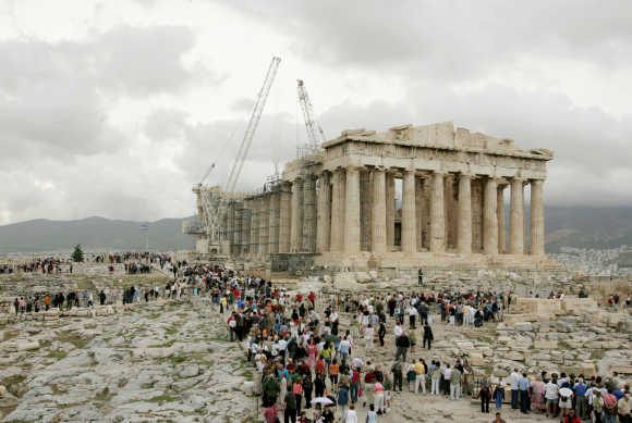 Tourists visit the temple of the Parthenon at the Acropolis hill in Athens.
