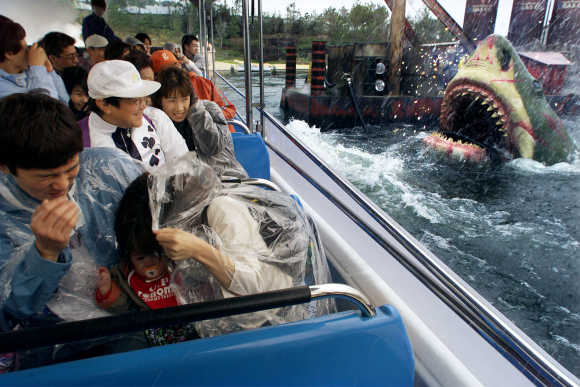 Japanese guests react as 'Jaws' emerges out of the water in a ride attraction at Universal Studios in Osaka, Japan.