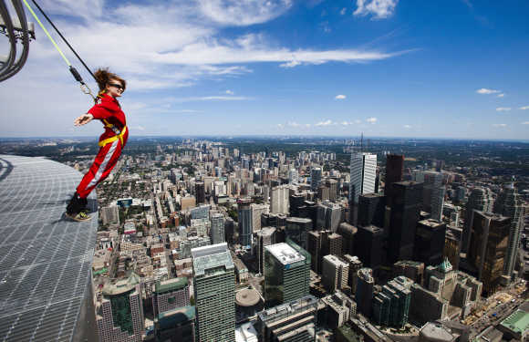 A reporter leans over the edge of the catwalk during the media preview for the 'EdgeWalk' on the CN Tower in Toronto.