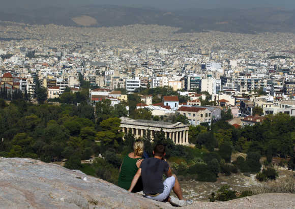 Tourists sit on a hill overlooking Athens outside the archaeological site in Athens, Greece.